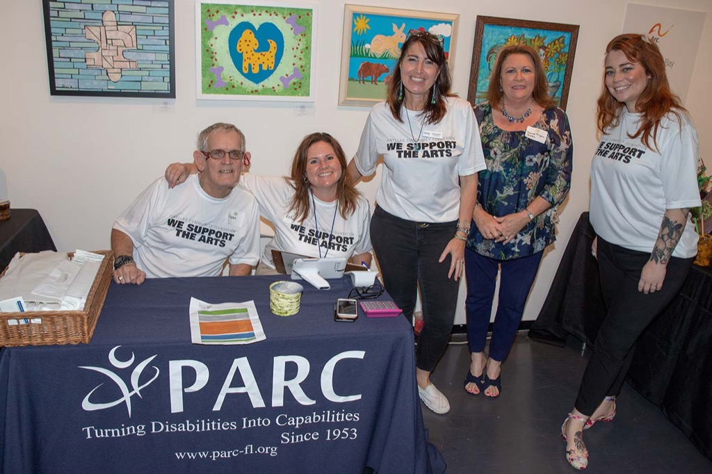 PARC volunteers stand by their table and artwork