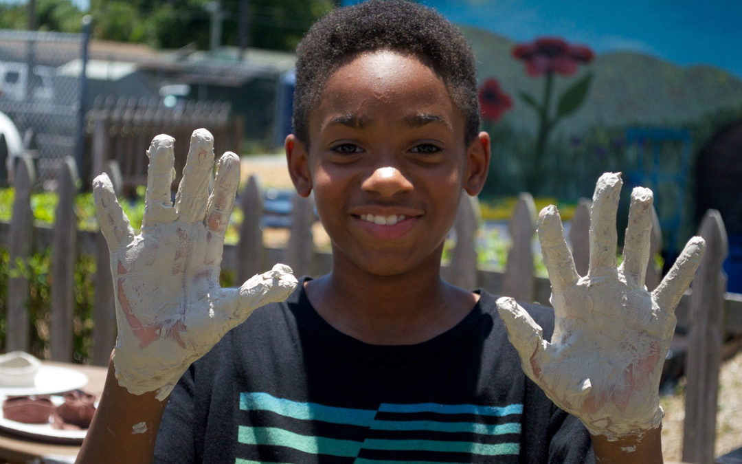 Young boy displays clay covered hands.
