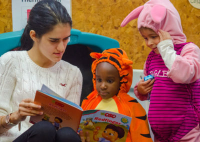 Preschool teacher reads to two students in costumes.