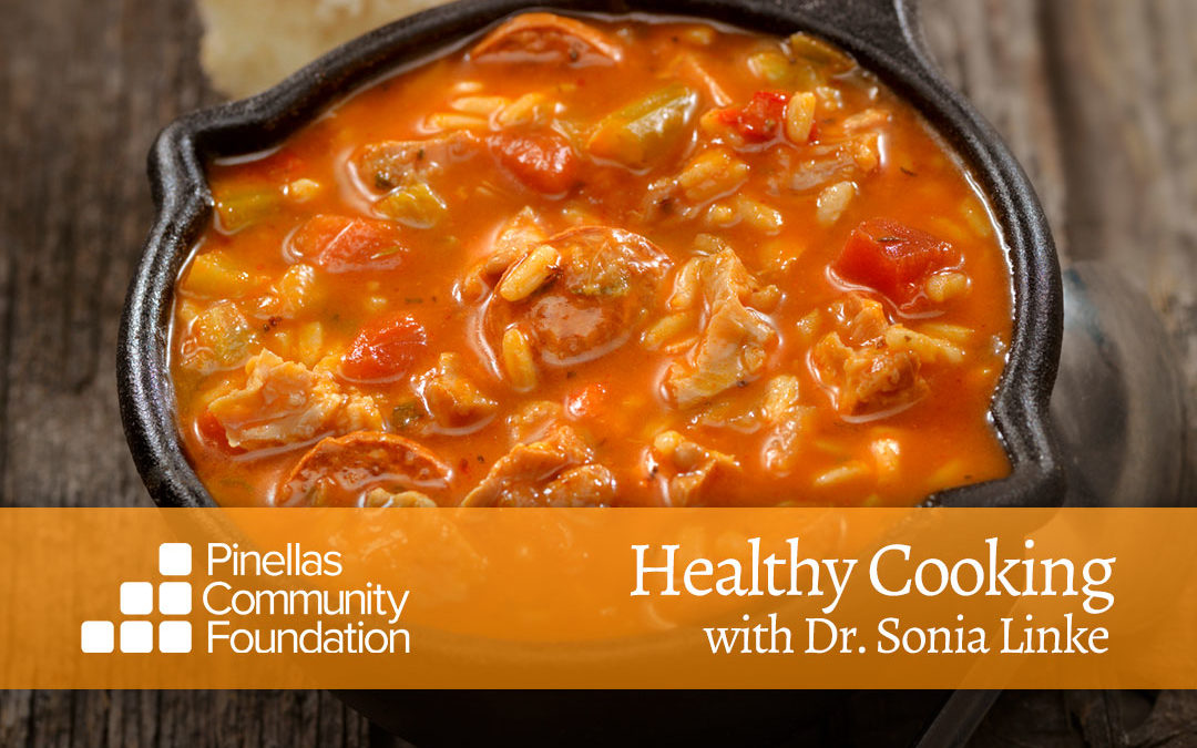 Healthy chicken stew with tomatoes, peppers, beans and rice in cast iron skillet.